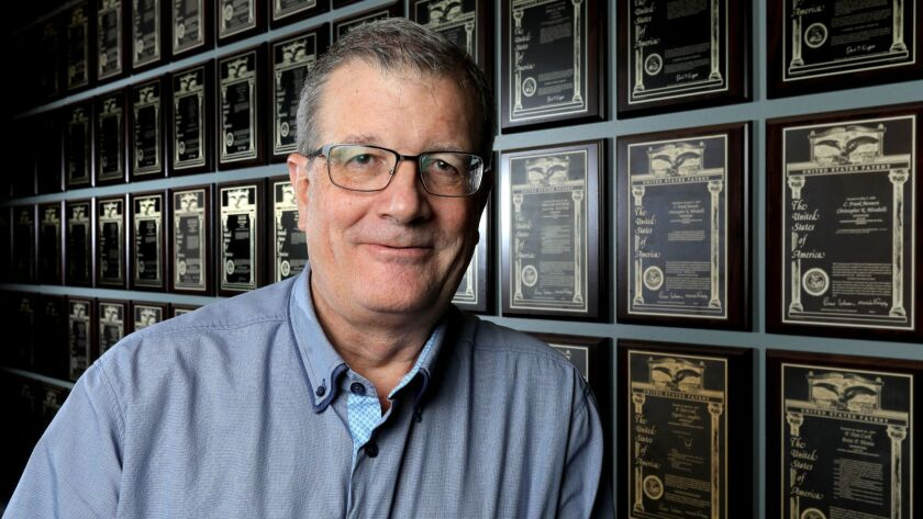 "Portrait of Frank Bennett, a researcher at Ionis Pharmaceuticals, with the company's ""patent wall,"" that displays the company's many patents."