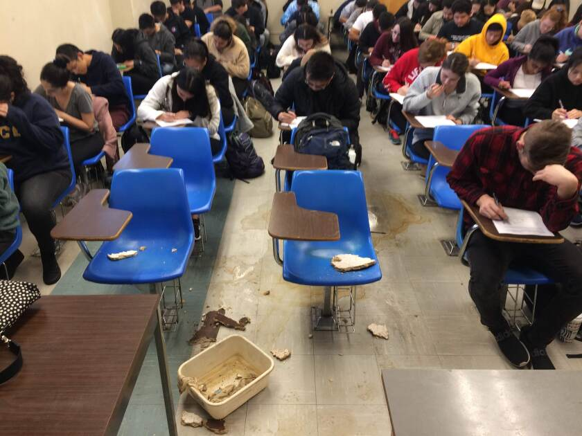 Broken pieces of ceiling tiles and water stains cover empty desks in the middle of a crowded classroom