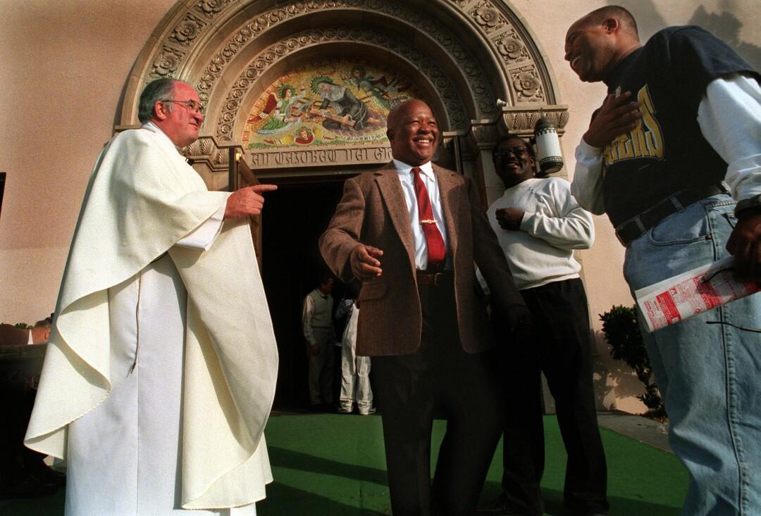 In 1999, following mass, Father Joe Carroll greets members from the St. Rita's Parish