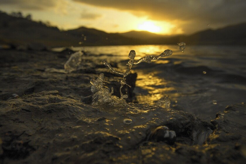 At sunrise, wind pushes the receding water to splash up on the banks at Pine Flat Reservoir in Sanger, Calif.