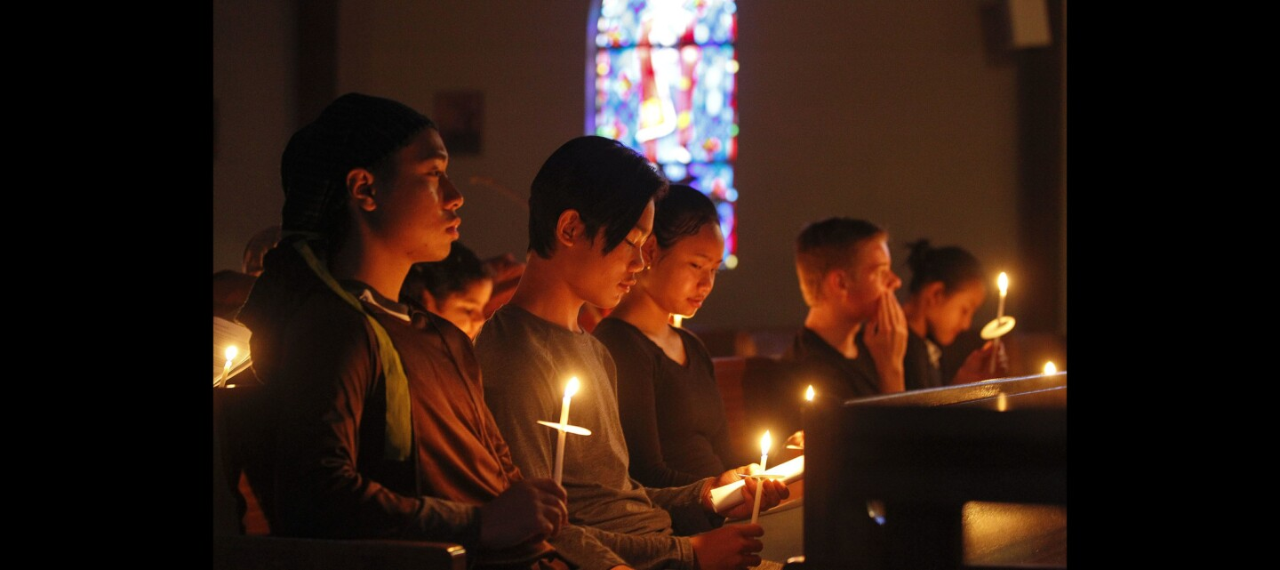 Hsa Moo, 17, left, Hsar Law, 12, second from left, and Dah Dah, 16, center, hold candles during the Easter Vigil Service at St. Alban's Episcopal Church.