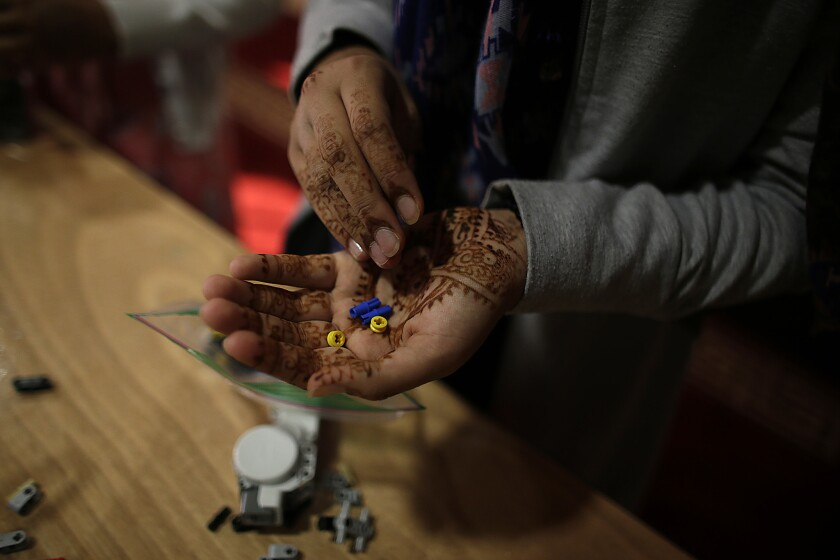 FemSTEM team member Sarah Khalid gathers Lego pieces during a September practice as she helps assemble a robotic vehicle.