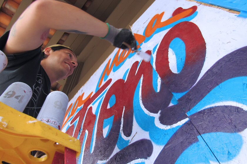 Artist Joe Castillo works on a mural at the La Mesa Spring Shopping Center. Many artists are painting murals at the La Mesa Springs Shopping Center and throughout downtown La Mesa, in the aftermath of protests that turned into riots, violence, tagging and looting in La Mesa late Saturday night and into Sunday morning.