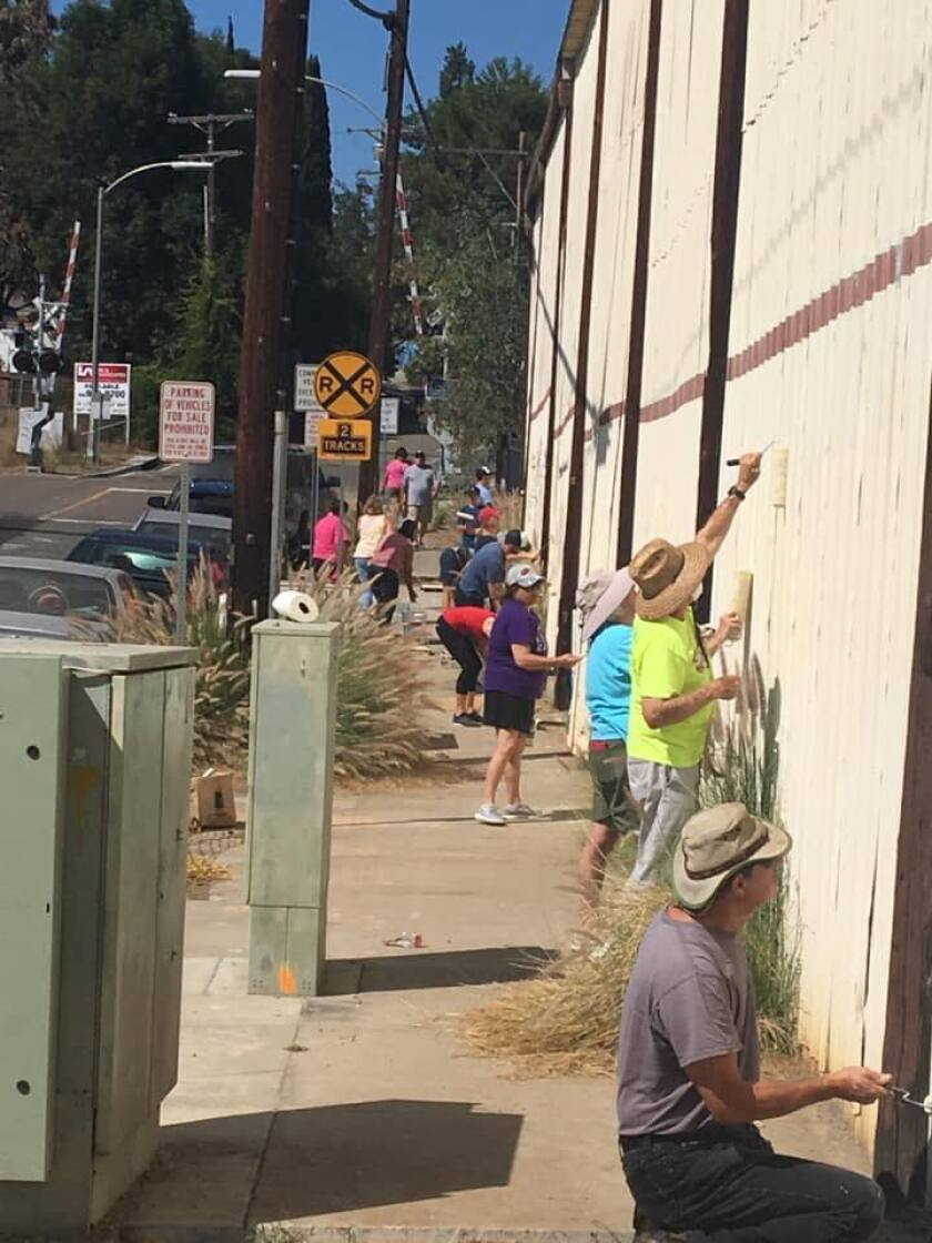 Dozens of Vista residents paint over the graffiti on the outside of the Geib True Value Lumber building at Santa Fe Avenue and Guajome Street in Vista on Saturday morning.