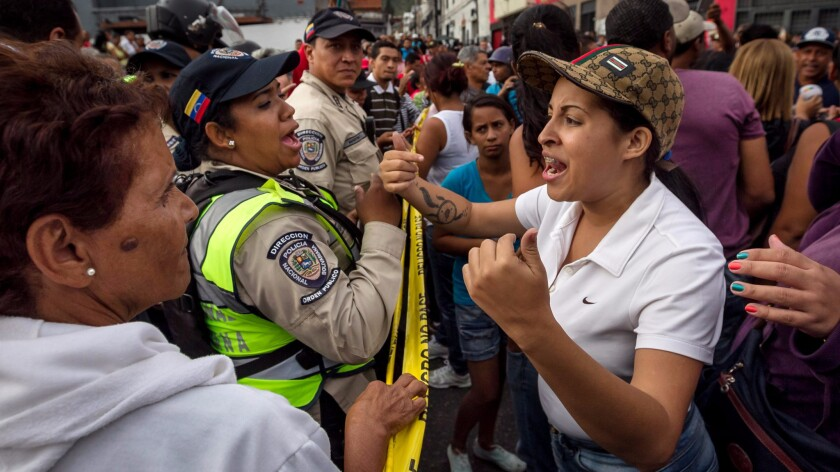 Venezuelans shout slogans in front of the authorities during a protest asking for food in the capital, Caracas. Protests and looting have occurred in several states because of the severe scarcity of food and medicines.