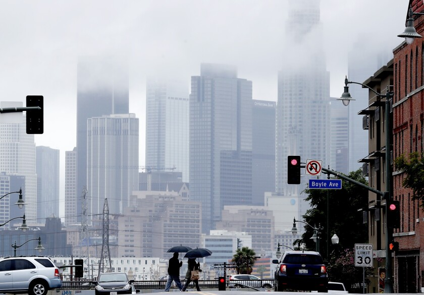 Pedestrians cross 1st Street in Boyle Heights as rain clouds partially obscure the downtown L.A. skyline during a storm in March.
