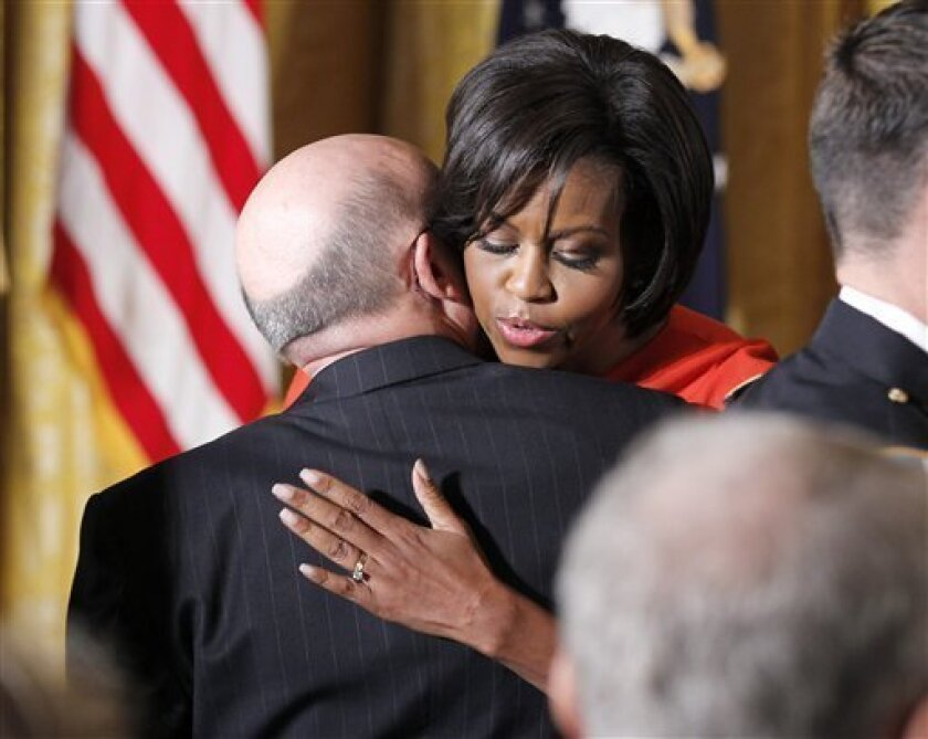 First lady Michelle Obama hugs Phil Miller, father of US Army Staff Sgt. Robert J. Miller, who received the Medal of Honor posthumously, Wednesday, Oct. 6, 2010, during a ceremony in the East Room of the White House in Washington. Miller received the honor for his heroic actions in Afghanistan on January 25, 2008, after displaying immeasurable courage and uncommon valor eventually sacrificing his own life to save the lives of his teammates and 15 Afghanistan National Army soldiers. (AP Photo/Pablo Martinez Monsivais)