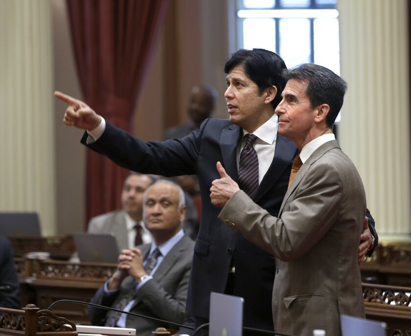 State Sen. Mark Leno, right, and Senate President Pro Tem Kevin de León watch as votes on the minimum wage bill are posted in the Capitol on March 31. The bill, which would raise the wage to $15 an hour by 2022, was approved by both houses of the Legislature.