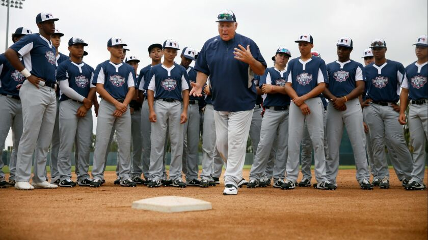LOS ANGELES, CA-JUNE 22, 2019: Mike Scioscia leads baseball players into a drill to step on the base