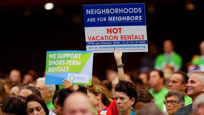 Neighborhood residents show their support and opposition to regulating short-term vacation rentals at a San Diego City Council meeting.