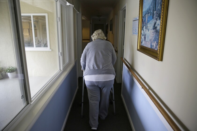 A woman walks to her room at a senior care home in Calistoga, Calif.