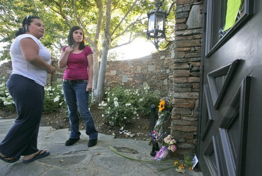 Michael Jackson fans Elia Barbosa, left, and Amanda Tongen read a farewell note at a makeshift memorial at the gates of the pop icon's old Neverland Ranch, in Los Olivos, Calif. Jackson died Thursday in Los Angeles at the age of 50.