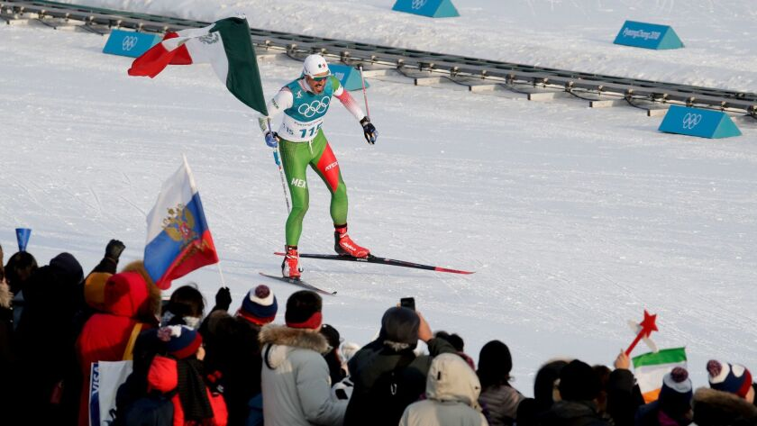 El mexicano Germán Madrazo, toma la bandera de su país luego terminar último en los 15 kilómetros li