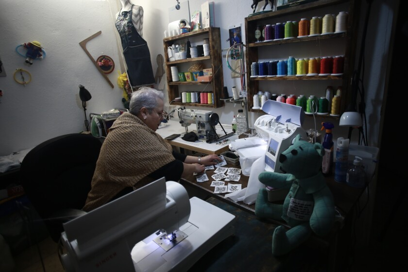 """Erendira Guerrero makes stuffed bears for people who lost a family member to COVID-19, using one of the deceased's articles of clothing, at her home workshop in Ciudad Juarez, Mexico, Monday, Jan. 11, 2021. """"Due to COVID-19, many people were left without closure, because they couldn't say goodbye to their family members. They need to close the circle. The bears are helping them,"""" said Guerrero. (AP Photo/Christian Chavez)"""