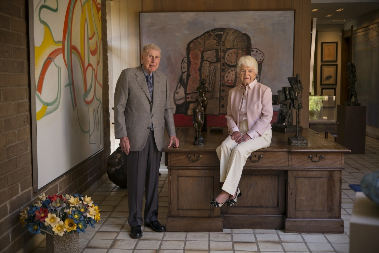 """Harry """"Hunk"""" and Mary """"Moo"""" Anderson pose in the foyer of their home with two paintings in the background. The Willem DeKooning, left, and Philip Guston, directly behind them, are both part of a collection they are donating to Stanford University."""