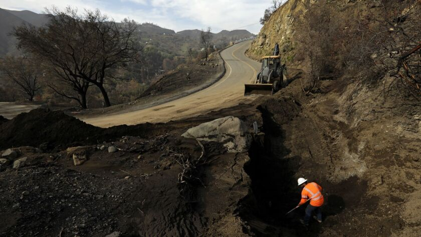 A Caltrans worker digs out dirt from around a storm drain on Decker Canyon, in preparation for the rain expected Saturday.