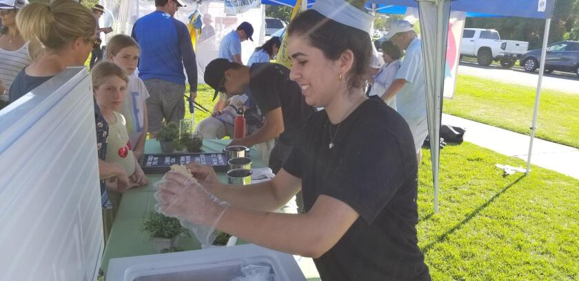 Leah Eslamian gets a scoop of Hammond's Gourmet Ice Cream for a concert-goer.