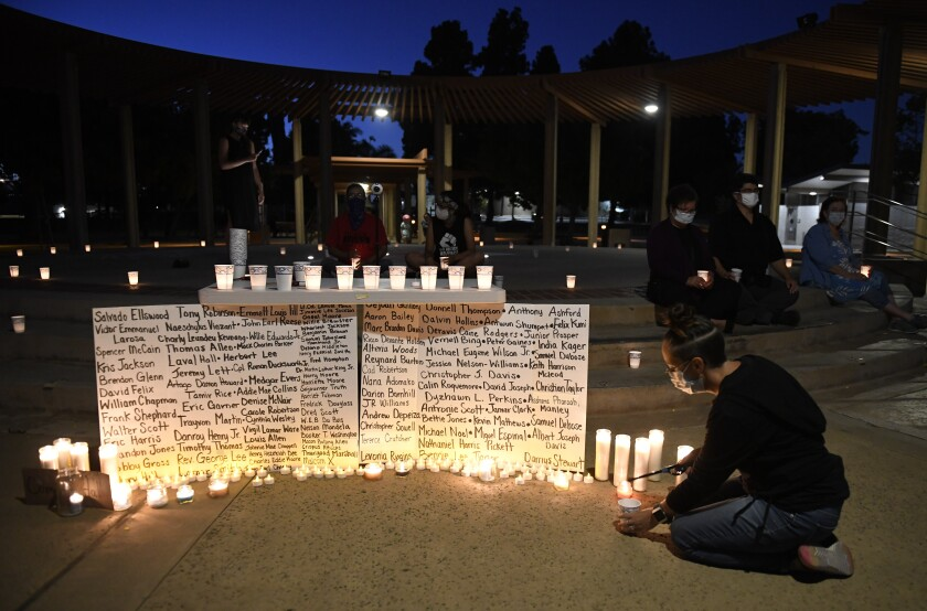 People light candles at a candlelight vigil held at Veteran's Park to protest police brutality