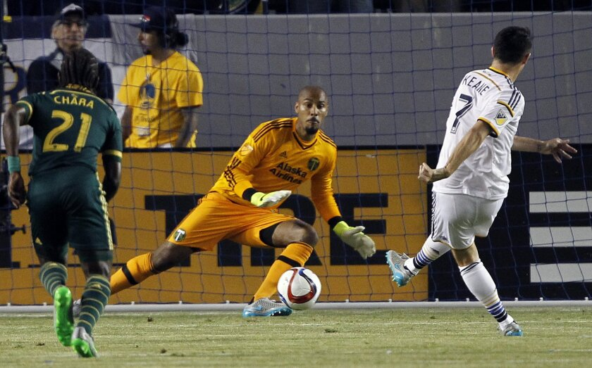 Los Angeles Galaxy forward Robbie Keane, right, scores on a penalty kick against Portland Timbers goalkeeper Adam Kwarasey, center, with midfielder Diego Chara (21) watching during the first half of an MLS soccer game in Carson, Calif., Wednesday, June 24, 2015. (AP Photo/Alex Gallardo)