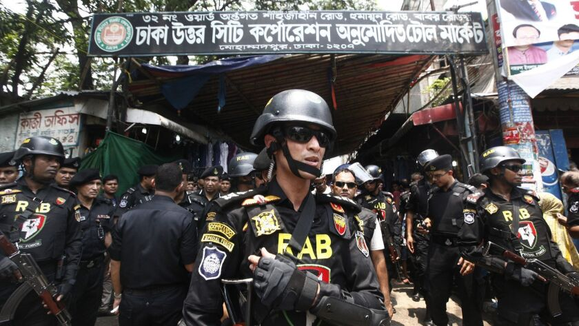 Bangladesh's Rapid Action Battalion (RAB) soldiers stand guard during a raid on suspected drug deale