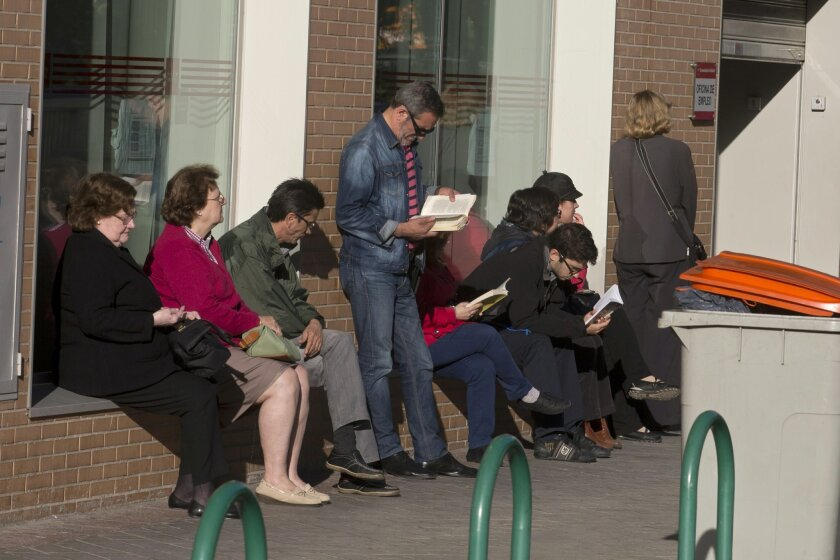 People wait for a government-run unemployment registry office to open, in Madrid, Spain, Tuesday, April 29, 2014. Spain's National Statistics Institute said the unemployment rate edged up to 25.9 percent in the first three months of the year from 25.7 percent in the previous quarter, a sign the recovery is still weak. The institute said Tuesday the number of people out of work fell by 2,300 in the January-March period, leaving the total number of unemployed at a rounded 5.9 million. (AP Photo/Paul White)