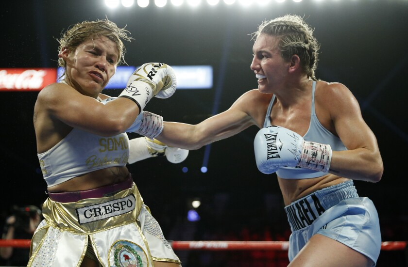 FILE - In this June 15, 2019, file photo, Mikaela Mayer, right, lands a right to Lizbeth Crespo in a boxing match in Las Vegas. Junior lightweight contender Mayer has tested positive for COVID-19 and has been pulled from the co-main event of Las Vegas' first major boxing card since the start of the coronavirus pandemic. (AP Photo/John Locher, File)