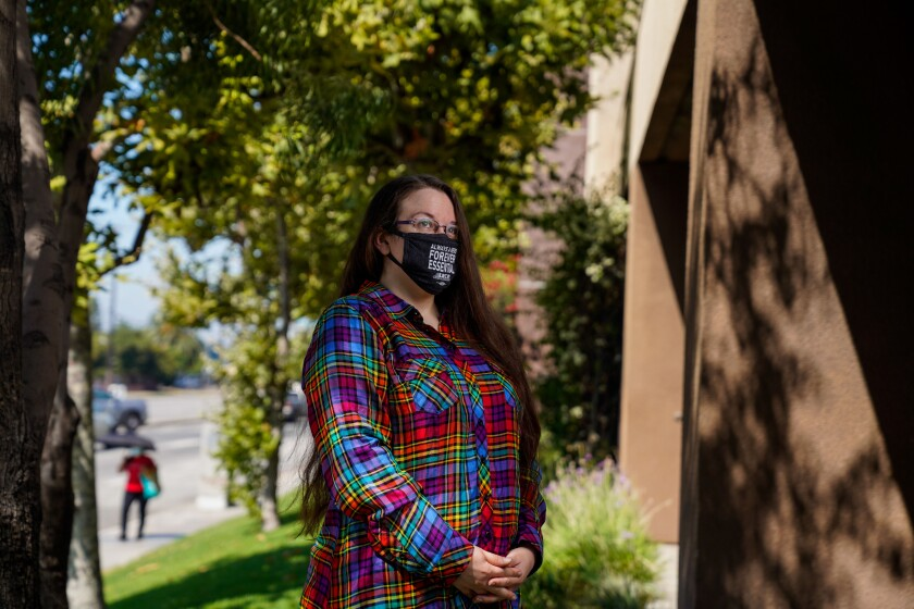 Mary Mueller-Reiche, a cashier at a Ralphs store in Mid-City, poses for a portrait outside while wearing a mask