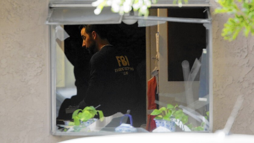 FBI agents search the Redlands home where the assailants in the San Bernardino mass shooting lived.