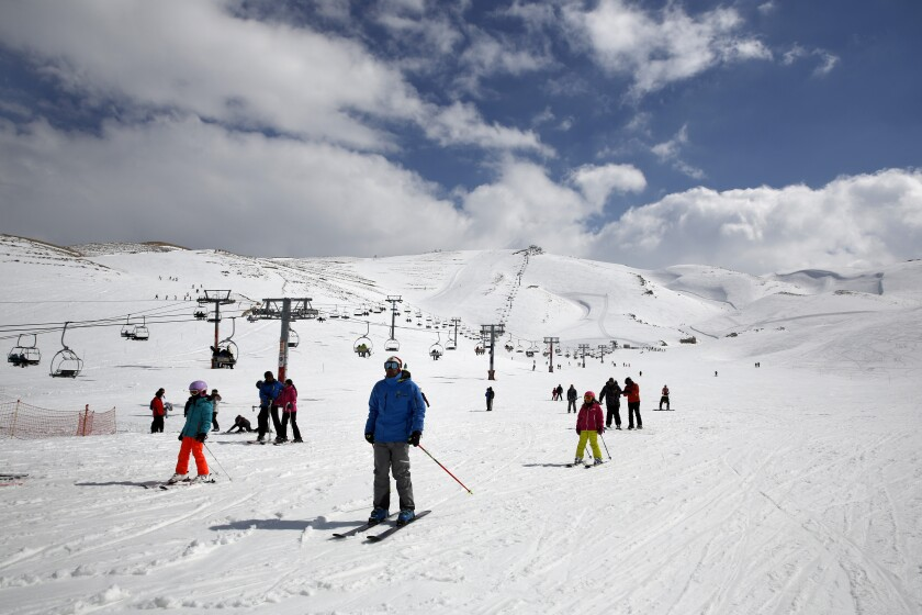 """FILE - In this Friday, Feb. 22, 2019 file photo, people ride ski lifts as other skiers slide down the hill on a sunny day at the Faraya-Mzaar ski resort, in Faraya, northeast of Beirut, Lebanon. As several countries have suspended access to the ski slopes to stop the spread of the coronavirus pandemic, the World Health Organization's emergencies chief said the risk of catching COVID-19 while skiing is likely minimal. """"I suspect many people won't be infected barreling down the slopes on their skis,"""" said Dr. Michael Ryan at a WHO news briefing on Monday, Nov, 30, 2020. (AP Photo/Bilal Hussein, file)"""