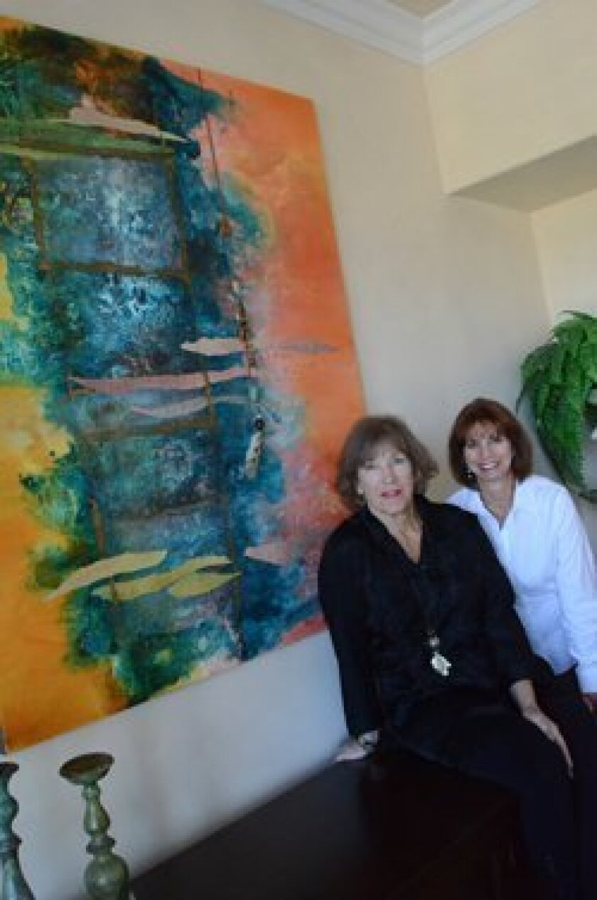 Artist Kate McCavitt and Realtor Marla Zanelli (with McCavitt's painting, 'Entering the Great Kiva,') teamed up to transform a house in Carlsbad.