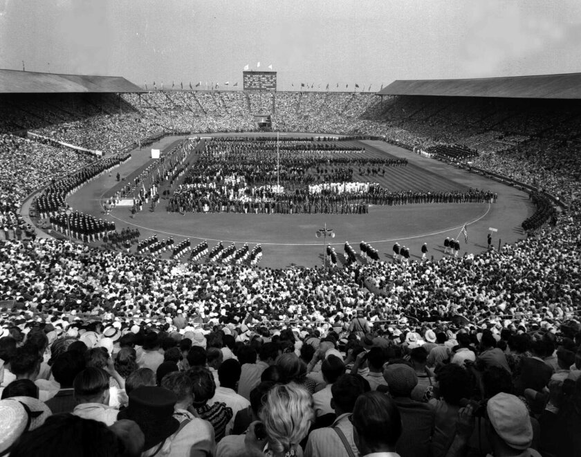 FILE - This July 29, 1948 file photo, showing the opening ceremony of the 1948 Olympic Games at Wembley Stadium, in London, England. London was still cleaning up bombing damage from World War II when it staged the Olympics in 1948. Britain was also struggling financially; food, clothing and gas were still being rationed. The athletes had to bring their own towels and, with housing in short supply, were accommodated in schools and Royal Air Force camps. The games were organized in less than two years, and despite the tiny budget it was a success, its legacies including greater sporting opportunities for women. (AP Photo, File )