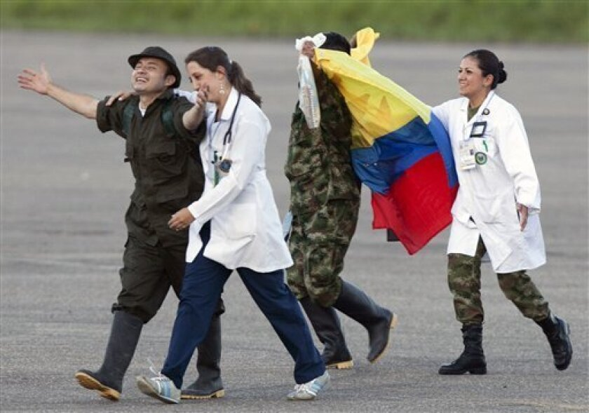 Accompanied by medical personnel, police sergeant Cesar Augusto Lasso, left, and army sergeant Luis Alfredo Moreno, third from left, gesture upon their arrival to an airport after being released by the Revolutionary Armed Forces of Colombia, or FARC, in Villavicencio Colombia, Monday, April 2, 2012. Colombia's main rebel group on Monday freed what it says were its last 10 soldier and police captives, all of whom had been held in jungle prisons for at least 12 years. (AP Photo/Fernando Vergara)