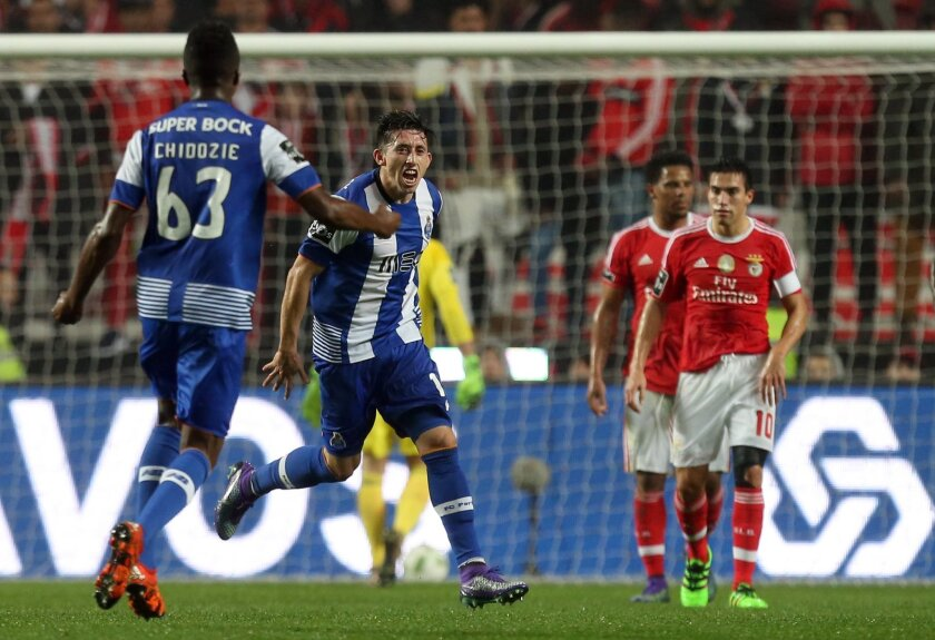Porto's Hector Herrera, center,  celebrates after scoring his side's first goal against Benfica during their Portuguese league soccer match at Benfica's Luz stadium in Lisbon, Friday, Feb. 12, 2016. (Armando Franca)