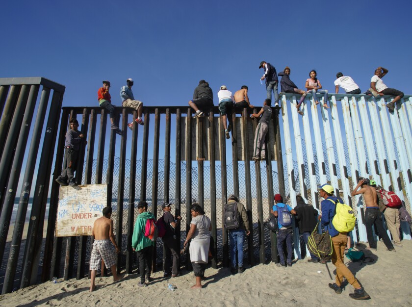 On arrival to the U.S.-Mexico border, many climbed the fence with U.S. Border Patrol on the north side of the fence observing.