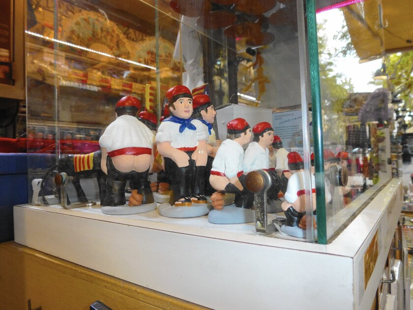 """Barcelona's traditional caganer figurines, also called """"poopers,"""" are sold at a kiosk. The Catalan folk-art personage, put in creches, is often portrayed as a famous figure."""