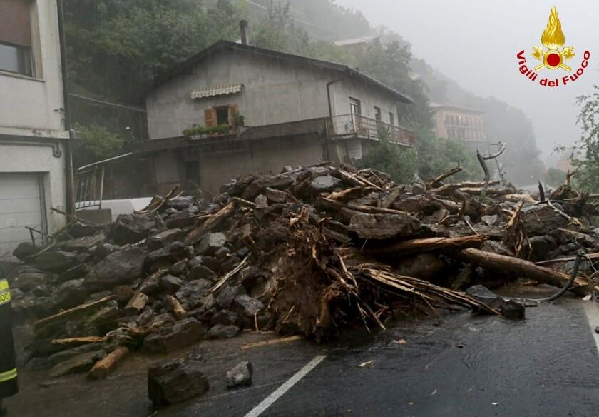 Unas ramas y rocas yacen sobre el asfalto luego de que un alud azotó una localidad cercana al lago de Como