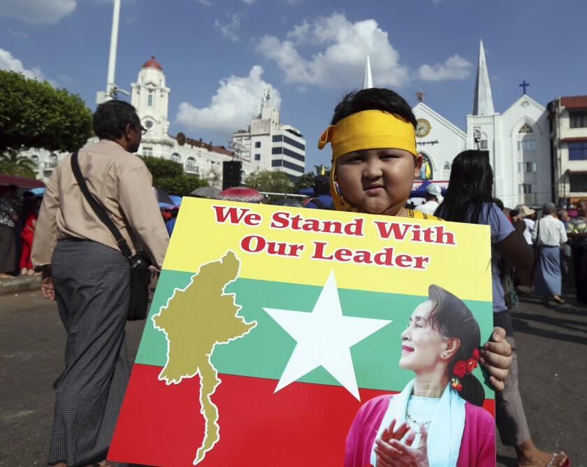 A boy with Karen ethnic attire holds placard with picture of Myanmar leader Aung San Suu Kyi during a rally Sunday, Dec. 1, 2019, in Yangon, Myanmar. About 700 people rallied Sunday to show support for Myanmar's leader, Aung San Suu Kyi, as she prepares to defend the country against charges of genocide at the U.N.'s highest court. (AP Photo/Thein Zaw)