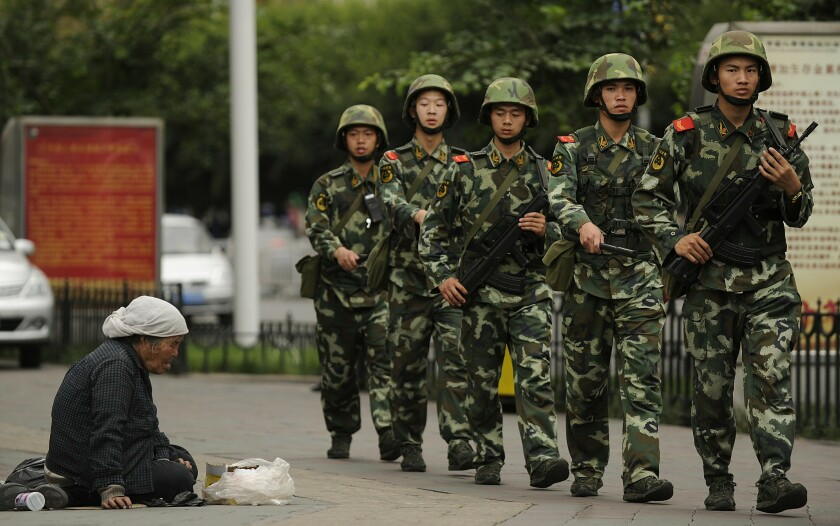 A Muslim Uighur woman begs as armed Chinese paramilitary policemen march past on a street in Urumqi on July 5, 2010.