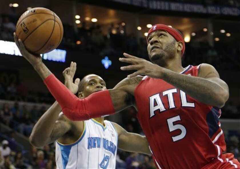 Atlanta Hawks small forward Josh Smith (5) shoots past the defense of New Orleans Hornets small forward Lance Thomas (42)during the second quarter of an NBA basketball game at the New Orleans Arena in New Orleans Tuesday, Jan. 1, 2013. (AP Photo/Dave Martin)