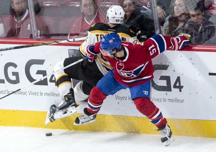 Boston Bruins' Zach Trotman (62) is checked into the boards by Montreal Canadiens' David Desharnais (51) during second period NHL hockey action, in Montreal, on Saturday, Nov. 7, 2015. (Paul Chiasson/The Canadian Press via AP)