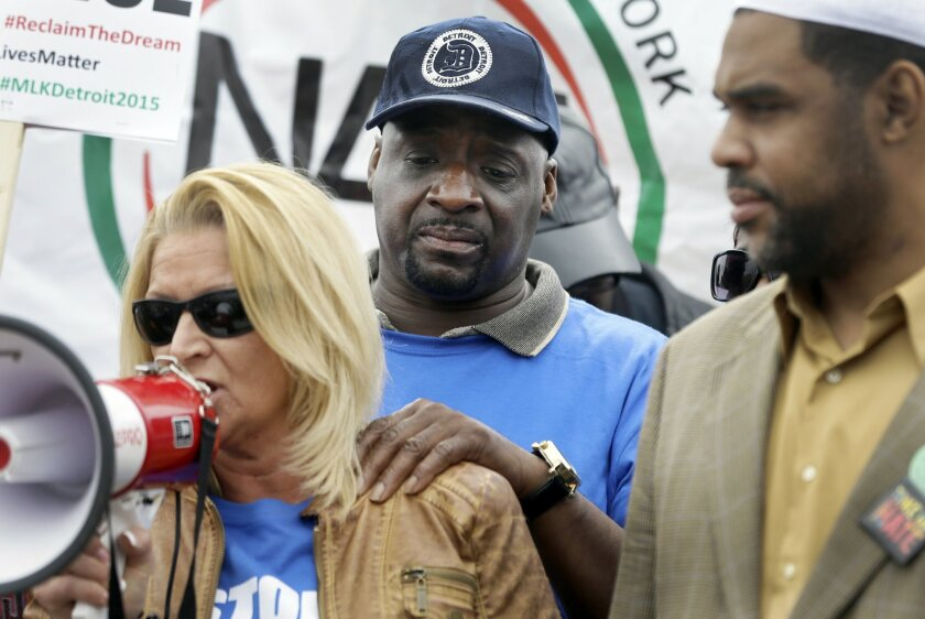 Floyd Dent, stands behind his attorney as she addresses hundreds of protesters after a march on Michigan Ave. on Friday, April 3, 2015 in Inkster, Mich. Dent was pulled from his car in January, repeatedly punched in the head by a white police officer and subdued with a stun gun in suburban Detroit. (AP Photo/Carlos Osorio)