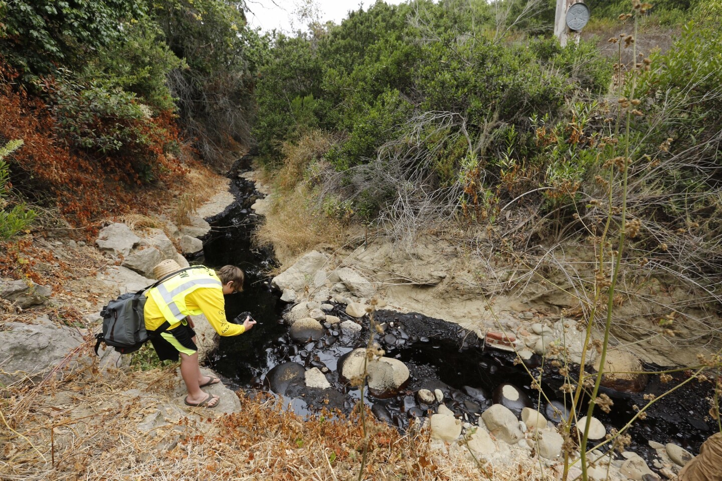 Gabriel Anderson, 13, photographs a section of the oil spill in Ventura. He was with his father, Sean Anderson, a professor at Cal State Channel Islands, who was collecting samples to test for toxicity.
