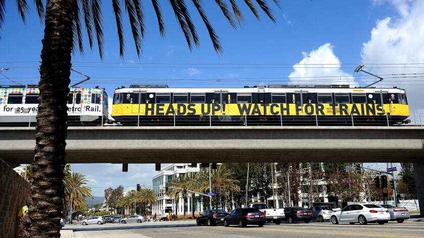 Santa Monica residents have proposed an initiative that would require voter approval for most development projects over 32 feet tall. Above, a new Expo Line test train rides over a bridge to the 26th Street/Bergamot station.