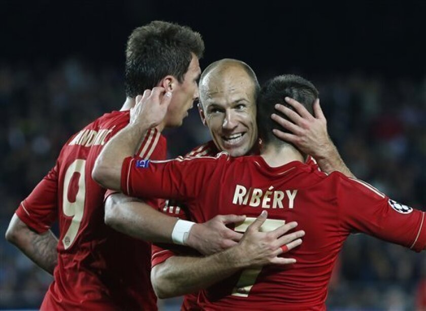 Bayern's Arjen Robben of the Netherlands, center, celebrates with Franck Ribery of France, right, and Mario Mandzukic of Croatia, left, their team's second goal during the Champions League semifinal second leg soccer match between FC Barcelona and Bayern Munich at the Camp Nou stadium in Barcelona, Spain, Wednesday, May 1, 2013. (AP Photo/Matthias Schrader)