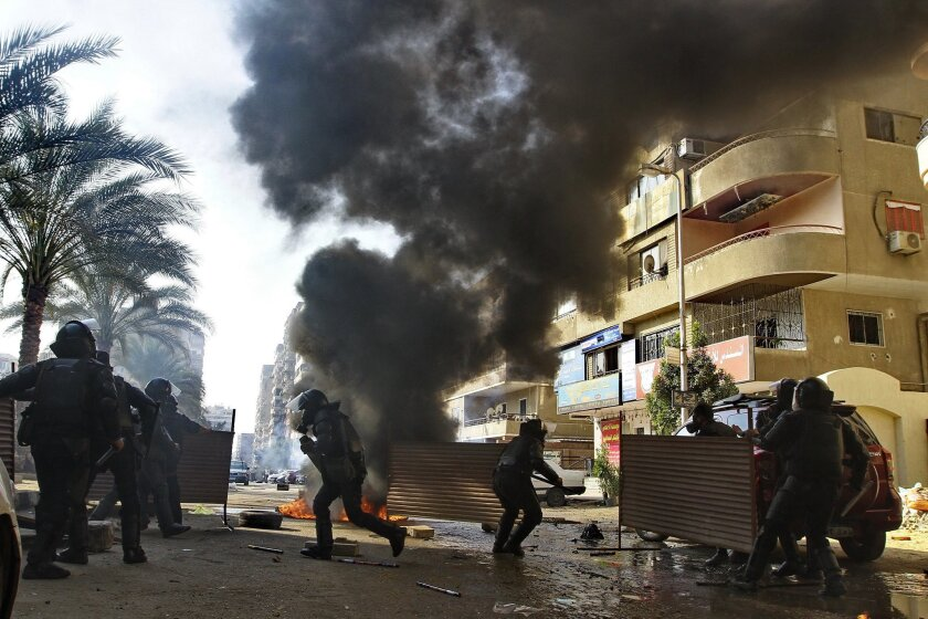 Egyptian security forces clash with supporters of ousted President Mohamed Morsi in the Nasr City district of Cairo, Egypt, Friday Jan. 10, 2014. Hundreds of Islamists rallied in Egypt's capital and across the country Friday, calling for a boycott of an upcoming constitutional referendum and clashing with security forces, with a bystander being killed, an official said. (AP Photo/Ahmed Abd El Latif, El Shouk Newspaper) EGYPT OUT