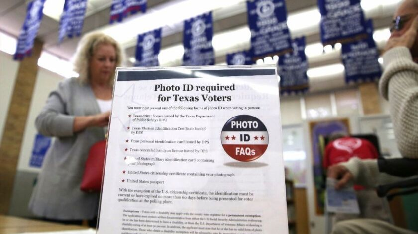 FILE - In this March 1, 2016, file photo, a sign tells voters of voter ID requirements before participating in the primary election at Sherrod Elementary school in Arlington, Texas.