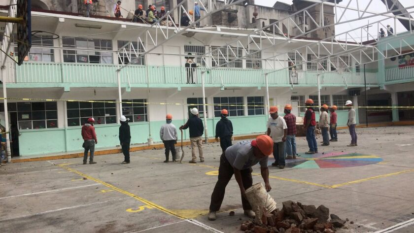Workers begin to remove rubble from the fallen cupola at Our Lady of Angels Church in Mexico City. M