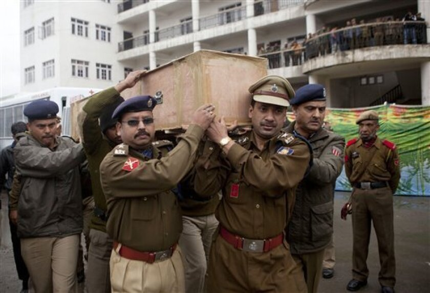 Indian paramilitary soldiers and police officers carry the coffins of their colleagues at the police headquarters in Srinagar, India, Thursday, March 14, 2013. Two militants carrying guns and grenades attacked a group of paramilitary soldiers on the outskirts of the capital of Indian-controlled Kashmir on Wednesday morning, leaving five soldiers and both militants dead and 10 other people wounded, police said. It was the bloodiest militant attack in the capital in years. (AP Photo/Dar Yasin)