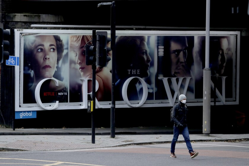 """FILE - In this file photo dated Friday, Nov. 20, 2020, a man wearing a face mask walks past a billboard advertising 'The Crown' television series about Britain's Queen Elizabeth II and the royal family, during England's second coronavirus lockdown, in London. Britain's Culture Secretary Oliver Dowden in a newspaper interview published Sunday Nov. 29, 2020, said he thinks """"The Crown"""" should come with a disclaimer as it's a work of fiction with historical liberties taken in the Netflix drama about the British royal family. (AP Photo/Matt Dunham, FILE)"""