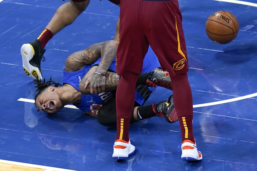 Orlando Magic guard Markelle Fultz screams and holds his knee after he was injured while going up for a shot against Cleveland Cavaliers defense during the first half of an NBA basketball game, Wednesday, Jan. 6, 2021, in Orlando, Fla. (AP Photo/John Raoux)